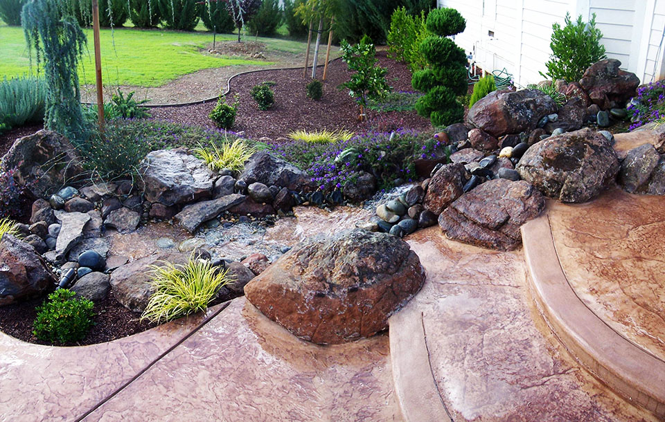 Roseville backyard rock stream water feature stamped for Landscaping rocks